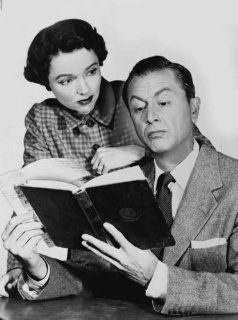 1955 Jane Wyatt looking over Robert Young's shoulder while he is reading a bo a7